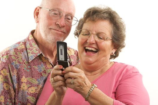 Senior Couple looks at the screen of a cell phone.