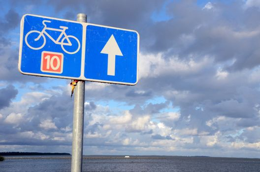 Bicycle path sign number ten 10 near lake and cloudy blue sky.