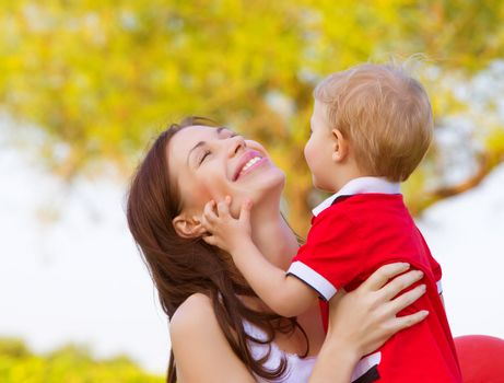 Picture of happy young mother playing game with cute little son outdoors in spring time, cheerful child with mom having fun on backyard, woman with small kid resting in the park in sunny day