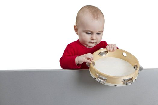young child holding tambourine behind grey shield. isolate on white background