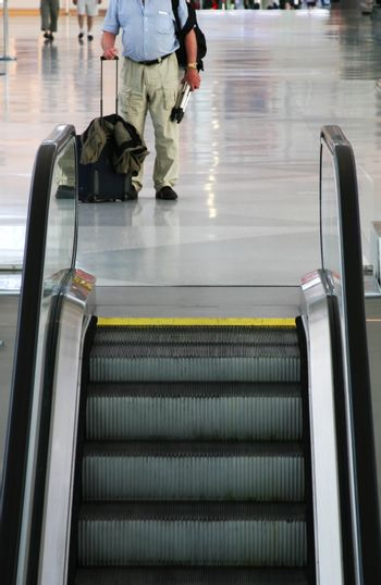 a bodyshot of a man standing by escalators in an airport with hand luggage