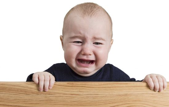 crying young child holding board. isolate on white background