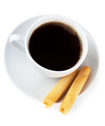 Cup of coffee with roll shaped cookies over white background