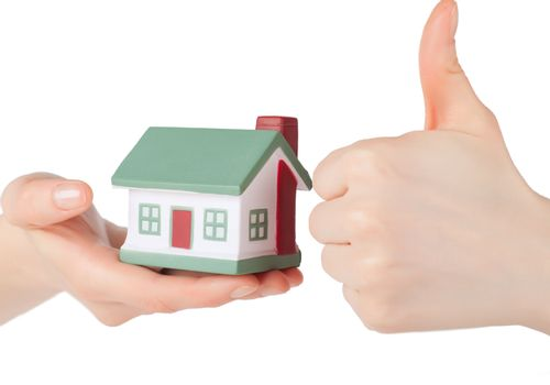 Little house toy in hands isolated over white background