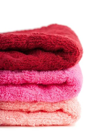 Stack of bright colorful towels over white background
