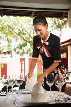 asian waitress setting table in restaurant