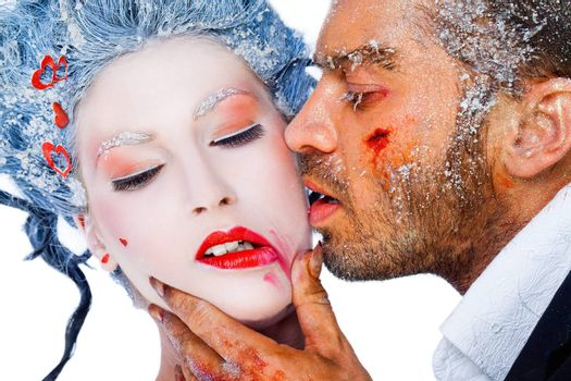 Male kissing female on cheek, smudging her lipstick - both faces with frozen makeup