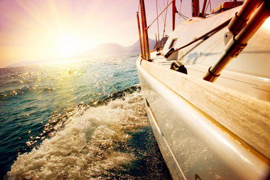 Yacht Sailing against sunset. Sailboat. Yachting