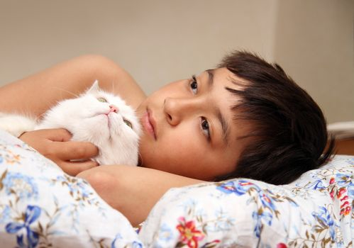 asian boy with white cat lieng in bed