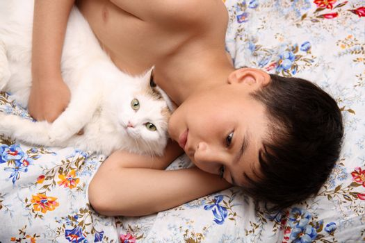 asian boy with cat lieng in bed
