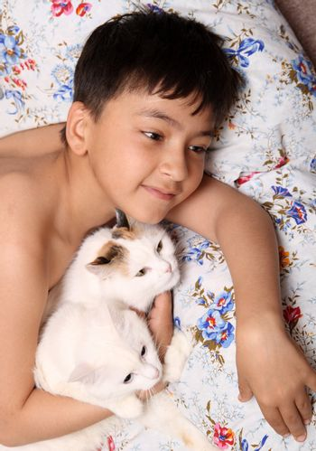 happy asian boy with cats lieng in bed
