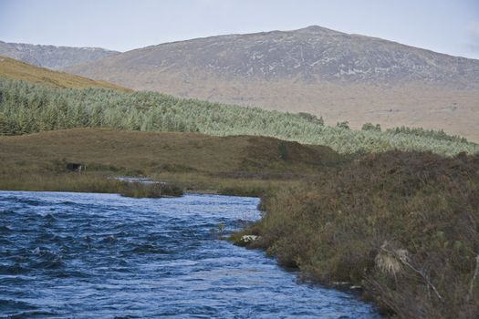 river in the scottisch highlands with mountain in background