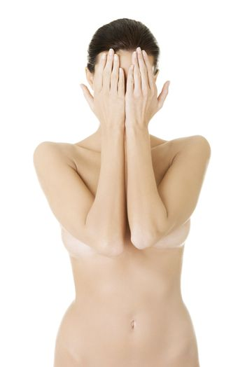 Nude woman covering face with hands