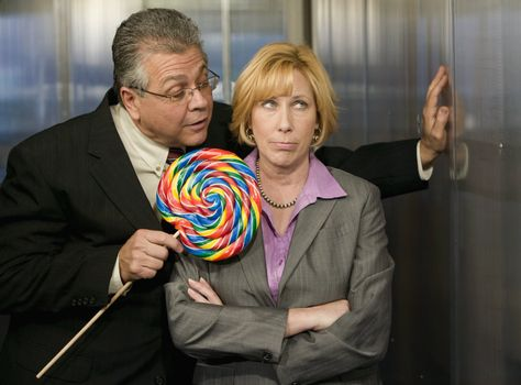 Man tempts woman with a big lollipop in an office