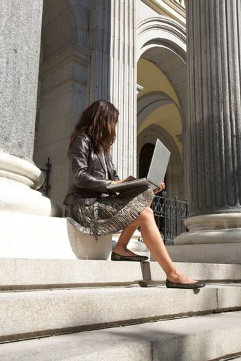 leather businesswoman sitting with portable