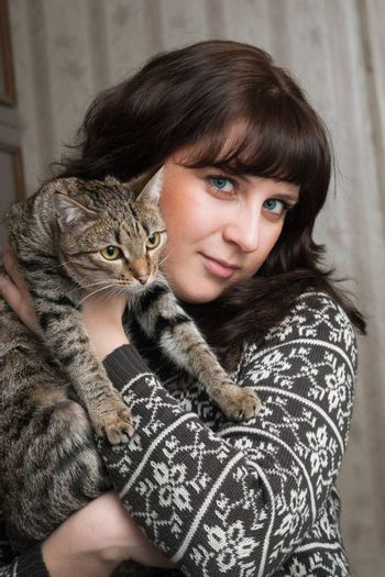 The girl holds on hands of a grey cat