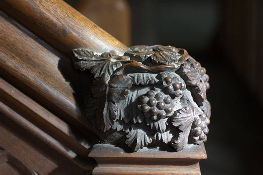 Detail (grapes) of wooden staircase to pulpit in Chetwode parish church, UK