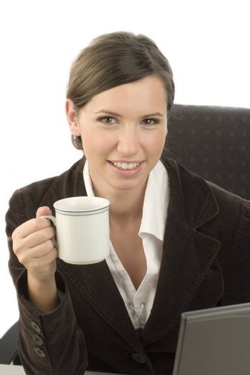 Young attractive woman with a cup of coffee in her hand and laptop in front of her