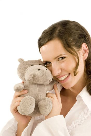 Smiling young woman with stuffed animal at her cheek