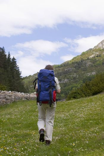 Woman with backpack hiking on a meadow in the mountains