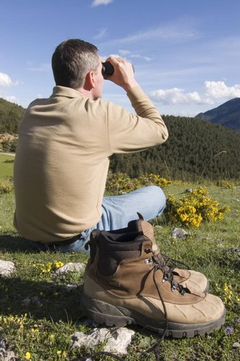 Man sitting in a meadow in the mountains looking through binoculars