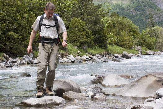 Man with backpack crossing a river in the mountains