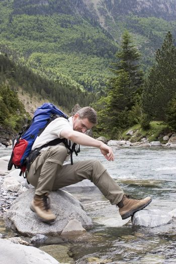 Man with backpack resting on a stone in a mountain river