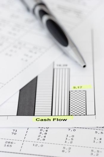 Business papers with ballpen focus on the words cash flow