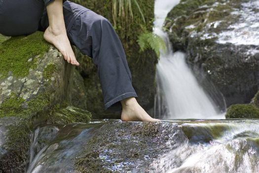 Woman sitting by a waterfall with a foot in the water