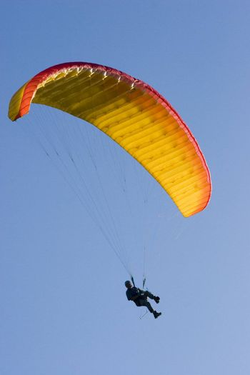 Orange paraglider in a blue sky