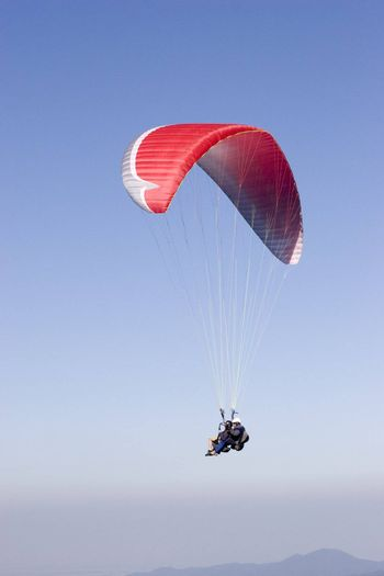 Two persons flying with a red paraglider against dark blue sky