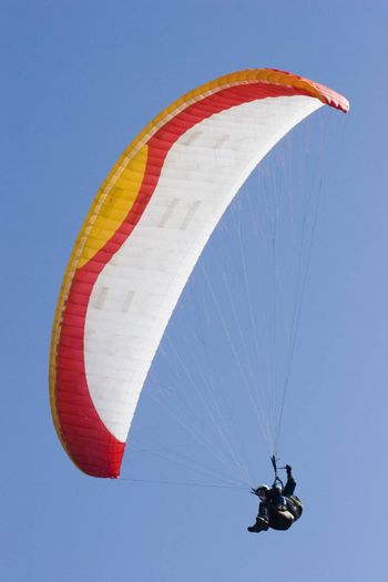 Colorful paraglider in front of a blue sky