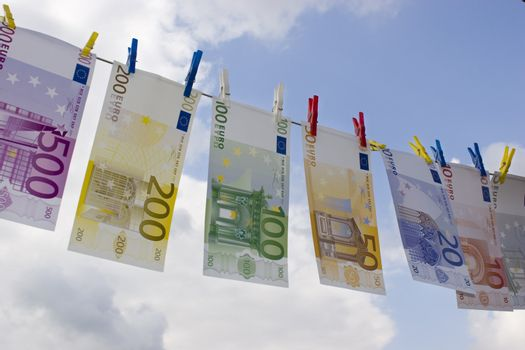 Euro banknotes on a clothesline against cloudy sky
