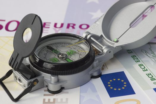 Compass lying on euro banknotes
