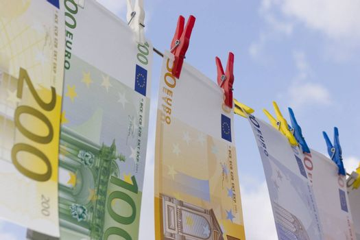 European banknotes on a clothesline against cloudy sky
