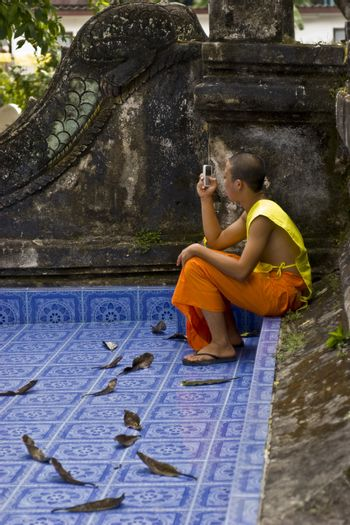 Young buddhist monk in a temple making a phone call