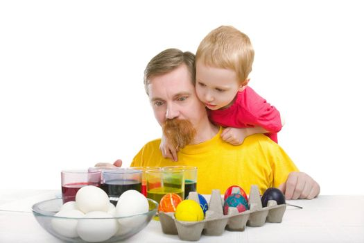 Man and boy look at paint and eggs