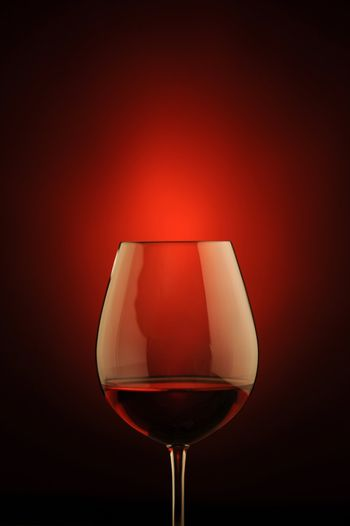 red wine glass , red light on background