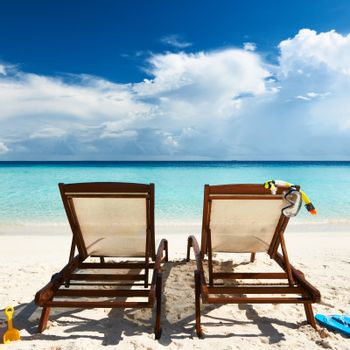Tropical beach with chaise lounge