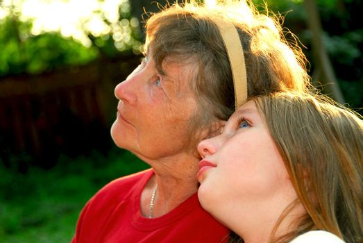 Portrait of grandmother and granddaughter in summer park looking up