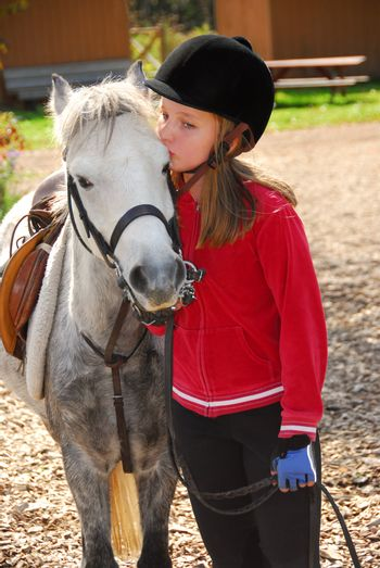 Portrait of a young girl with a white pony