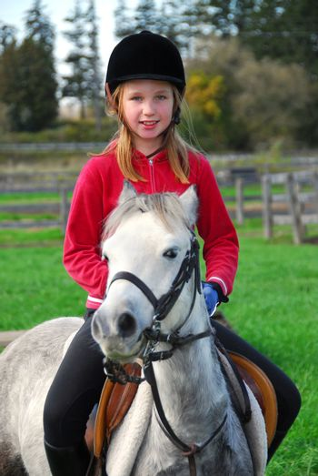 Young girl riding a white pony at countryside