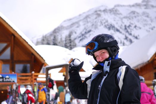 Young girl holding a snowball in front a chalet at downhill ski resort