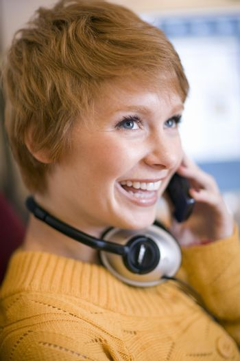 Young smiling woman talking on cell phone with headphones around her neck