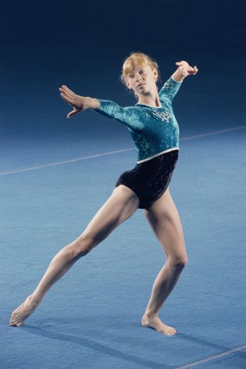Attractive young female gymnast performs floor routine