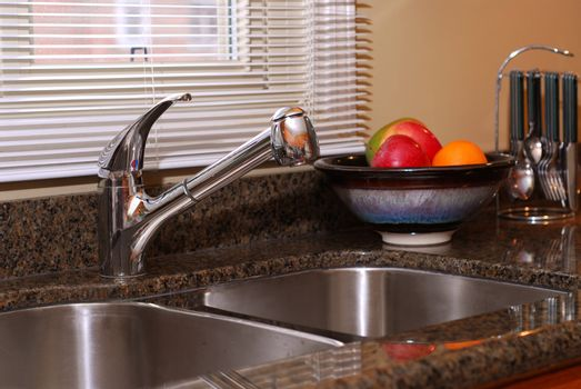 Interior of a modern kitchen with granite counter top and stanless steel double sink