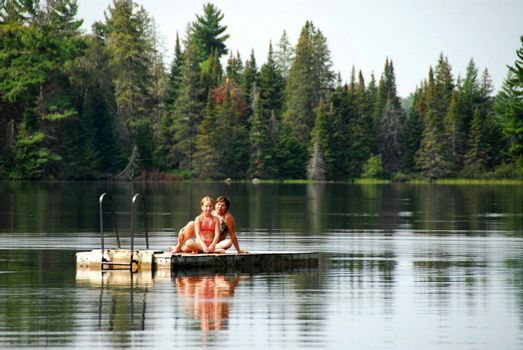 Grangmother and granddaughter sitting on a diving platform on a scenic lake
