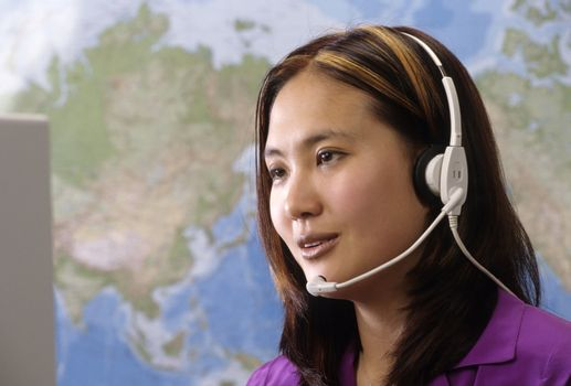 Woman wearing headset with map of world