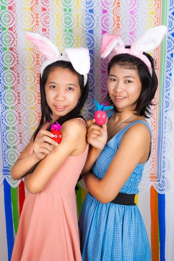 Cute Asian bunny girls hold Easter eggs in front of colorful flower shaped backdrop.