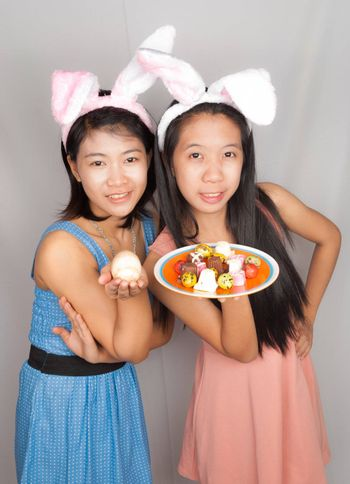 Cute Asian bunny girls hold plate of Easter eggs, chocolate and rock egg.
